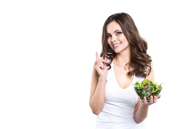 Uśmiechnięta kobieta trzyma zdrowy posiłek sałatkowy