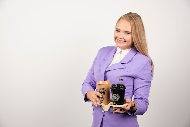Uśmiechnięta kobieta trzymająca dwie filiżanki kawy na białym tle