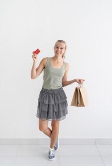 Uśmiechnięta kobieta trzymająca ekologiczne torby na zakupy i kartę kredytową