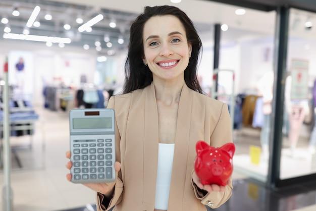 Uśmiechnięta kobieta trzymająca kalkulator i skarbonkę na tle centrum handlowego