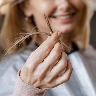 Uśmiechnięta kobieta trzymająca kępkę włosów, które przeciął jej fryzjer