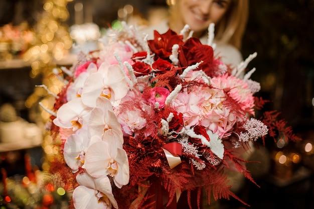 Uśmiechnięta kobieta trzymająca ogromne pudełko ozdobione taśmą w różowe orchidee i hydrandy z czerwonym zdobieniem