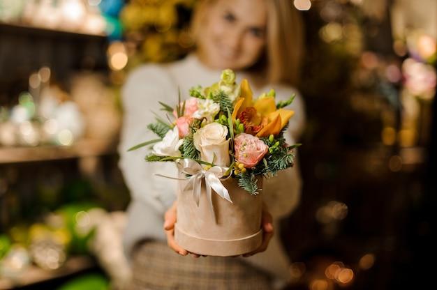 Uśmiechnięta kobieta trzymająca pudełko koloru brzoskwini z różowymi różami i żółtą orchideą ozdobioną gałęziami jodły