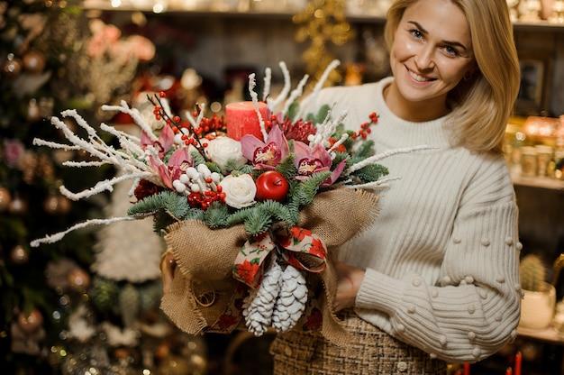Uśmiechnięta kobieta trzymająca świąteczną kompozycję z różowymi orchideami, białymi różami, gałęziami jodły, czerwonym jabłkiem i świecą w worze w kwiaciarni