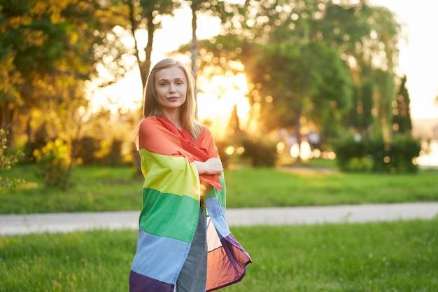 Uśmiechnięta kobieta trzymająca tęczową flagę na ramionach