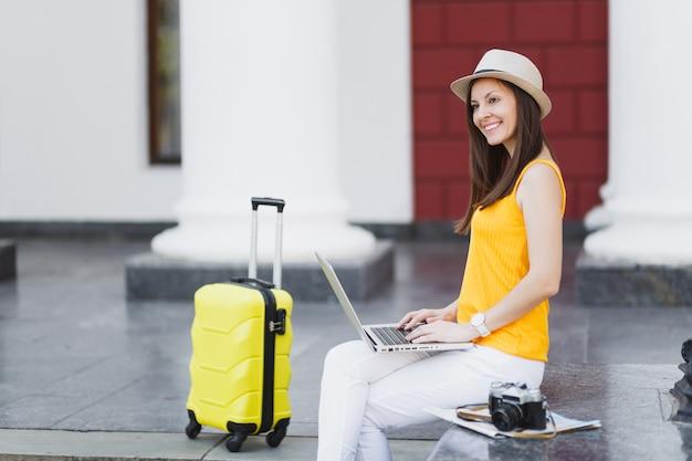 Uśmiechnięta kobieta turysta podróżnik w ubraniach casual, kapelusz z walizką siedzieć przy pracy na komputerze typu laptop w mieście na świeżym powietrzu. dziewczyna wyjeżdża za granicę na weekendowy wypad. styl życia podróży turystycznej.