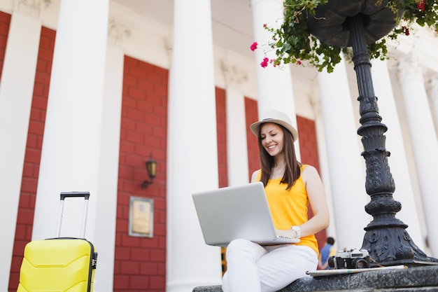 Uśmiechnięta kobieta turystyczna podróżnik w ubraniach casual, kapelusz z walizką siedzącą za pomocą pracy na komputerze typu laptop w mieście na świeżym powietrzu. dziewczyna wyjeżdża za granicę na weekendowy wypad. styl życia podróży turystycznej.