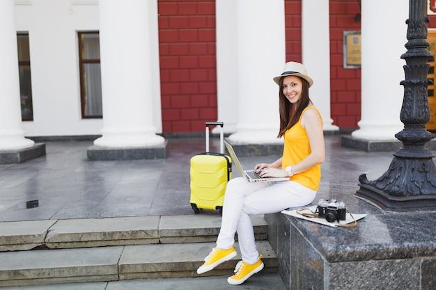 Uśmiechnięta kobieta turystyczna podróżnik z walizką siedzieć na schodach, korzystając z pracy na komputerze typu laptop w mieście na zewnątrz. dziewczyna wyjeżdża za granicę na weekendowy wypad. koncepcja życia podróż turystyka.