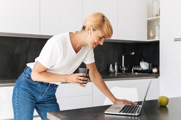 Uśmiechnięta kobieta ubrana casualy przy użyciu komputera przenośnego, stojąc w kuchni, nosząc słuchawki