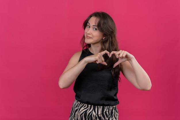Uśmiechnięta kobieta ubrana w czarny podkoszulek pokazuje gest serca na różowej ścianie