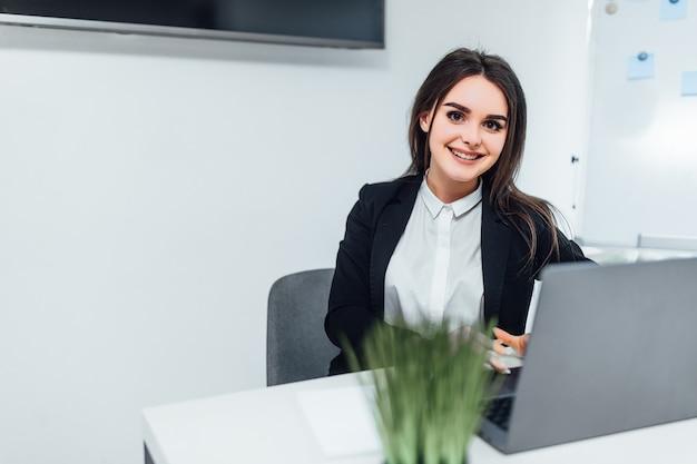 Uśmiechnięta kobieta ubrana w garnitur dorywczo siedzi w nowoczesnym biurze i za pomocą laptopa. z miejscem na kopię.