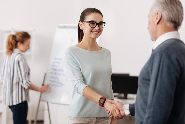 Uśmiechnięta kobieta ubrana w inteligentne zegarki dotykające rąk ze swoim partnerem, stojąc naprzeciw niego