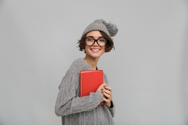 Uśmiechnięta kobieta ubrana w sweter i ciepły kapelusz gospodarstwa książki.