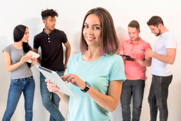 Uśmiechnięta kobieta używa cyfrową pastylkę z jej przyjaciółmi stoi behind