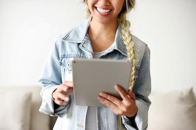 Uśmiechnięta kobieta używa cyfrową pastylkę