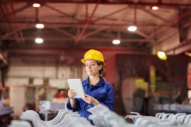 Uśmiechnięta kobieta używa cyfrowej pastylkę przy fabryką