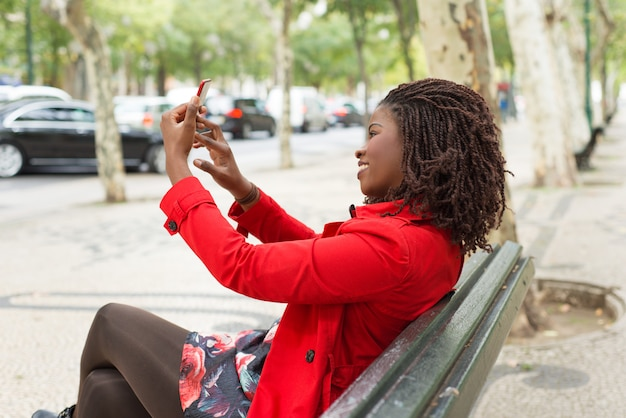 Uśmiechnięta kobieta używa smartphone w parku