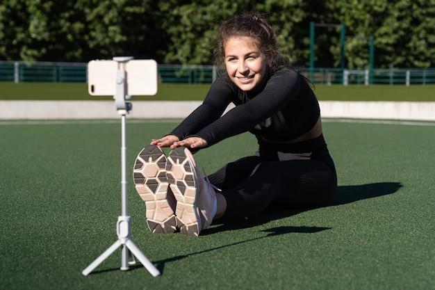 Uśmiechnięta kobieta vlogger w odzieży sportowej siedzi na sztucznej murawie na świeżym powietrzu