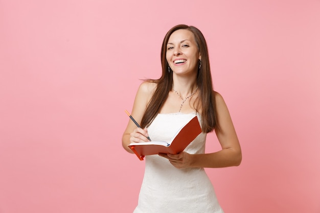 Uśmiechnięta kobieta w białej sukni pisze notatki w pamiętniku, zeszycie