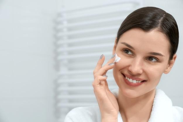 Uśmiechnięta kobieta w białej szacie przy użyciu kremu do twarzy w łazience