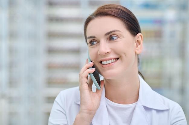 Uśmiechnięta kobieta w białym fartuchu komunikująca się przez smartfon