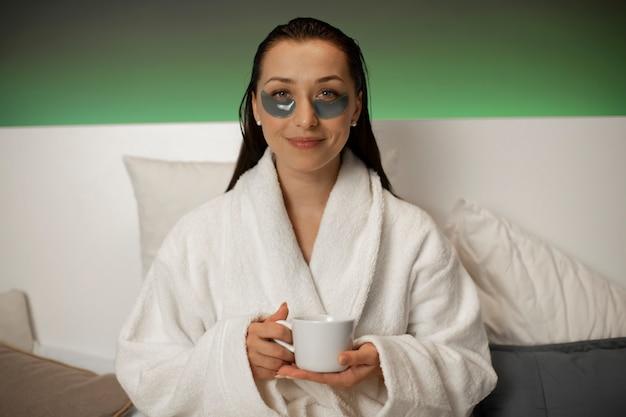 Uśmiechnięta kobieta w białym szlafroku robi zabiegi kosmetyczne w centrum odnowy biologicznej spa