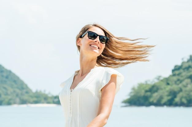 Uśmiechnięta kobieta w biel sukni pozyci na plaży. słoneczny letni dzień