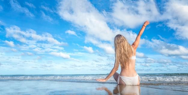 Uśmiechnięta kobieta w bikini obsiadaniu na tropikalnej plaży, szczęśliwa kobieta w swimwear białym kolorze cieszy się wakacje letnich kłama na białym piasku przeciw niebieskiemu niebu.
