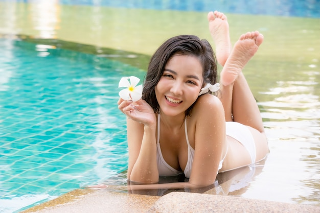 Uśmiechnięta kobieta w bikini siedzi na tropikalnym basenie, szczęśliwa kobieta w białym stroju kąpielowym, ciesząc się letnie wakacje w basenie.