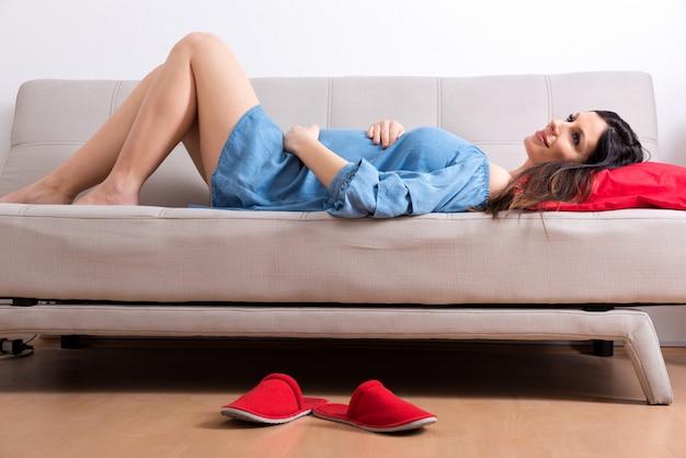 Uśmiechnięta kobieta w ciąży leżąca na kanapie w eleganckiej sukni