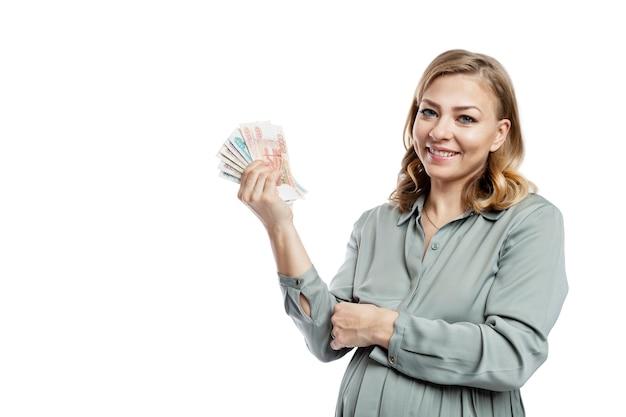 Uśmiechnięta kobieta w ciąży z pieniędzmi w dłoniach