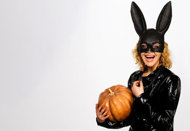 Uśmiechnięta kobieta w czarnej masce królika z dynią. 31 października. seksowna dziewczyna w kostiumie na halloween z jack-o-lantern.