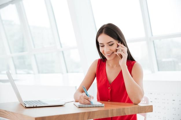 Uśmiechnięta kobieta w czerwonej koszuli siedzi przy stole z laptopem, pisze coś i rozmawia przez telefon w biurze