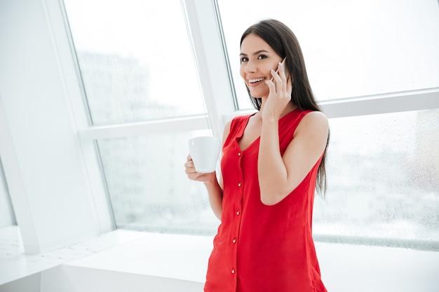 Uśmiechnięta kobieta w czerwonej koszuli z kawą rozmawiająca przez telefon i stojąca przy oknie