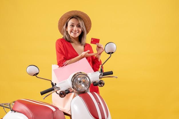 Uśmiechnięta kobieta w czerwonej sukience na motorowerze trzymająca torby na zakupy i kartę