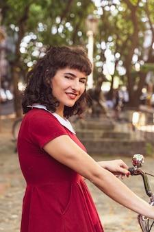 Uśmiechnięta kobieta w czerwonej sukience z rowerem