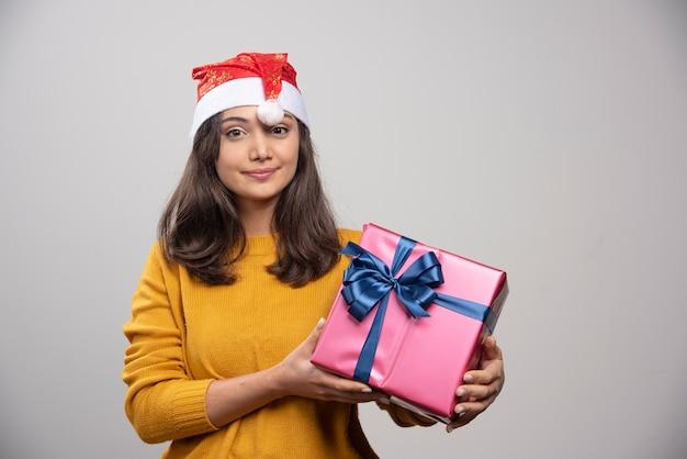 Uśmiechnięta kobieta w czerwonym kapeluszu świętego mikołaja z prezentem.
