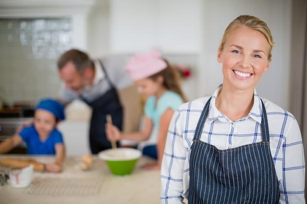 Uśmiechnięta kobieta w fartuch pozyci przy kuchnią