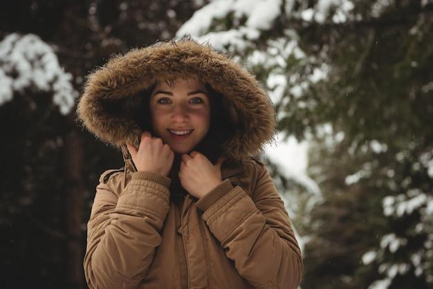 Uśmiechnięta kobieta w futrzanej kurtce zimą