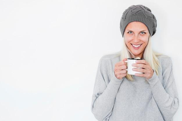 Uśmiechnięta kobieta w kapeluszowym trzyma gorącym napoju