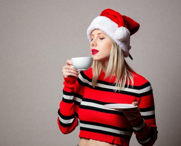 Uśmiechnięta kobieta w kapeluszu boże narodzenie z filiżanką kawy na szarej ścianie