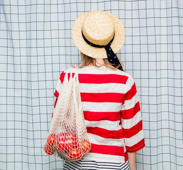 Uśmiechnięta kobieta w kapeluszu i pasiastej kurtce z torbą netto