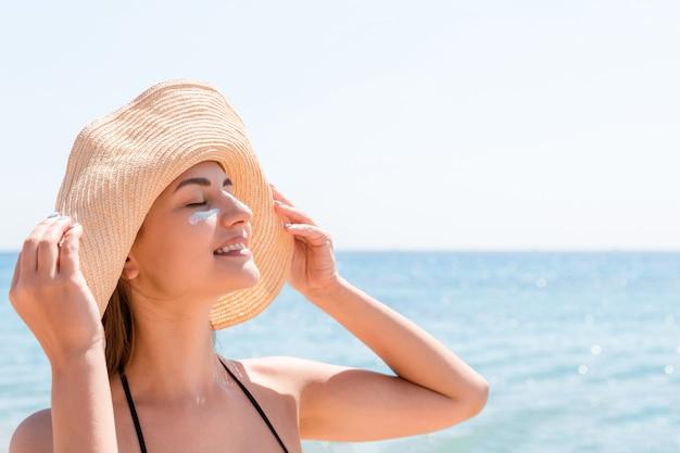 Uśmiechnięta kobieta w kapeluszu nakłada krem przeciwsłoneczny na twarz. styl indyjski.