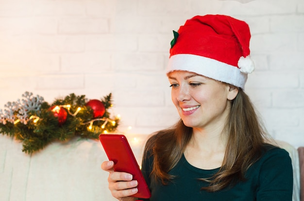 Uśmiechnięta kobieta w kapeluszu santa za pomocą telefonu komórkowego na wakacje nowego roku.