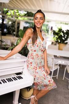 Uśmiechnięta kobieta w kolorowej letniej sukience stojącej w pobliżu fortepianu, fryzura z ogonem, obcasy, moda, plener, impreza, wydarzenie, idealne ciało, niesamowity wygląd, makijaż, uroczy