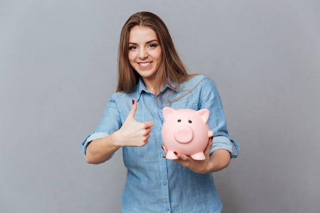 Uśmiechnięta kobieta w koszuli gospodarstwa skarbonka w ręku