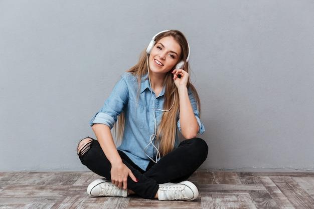 Uśmiechnięta kobieta w koszulowym słuchaniu muzyka na podłoga