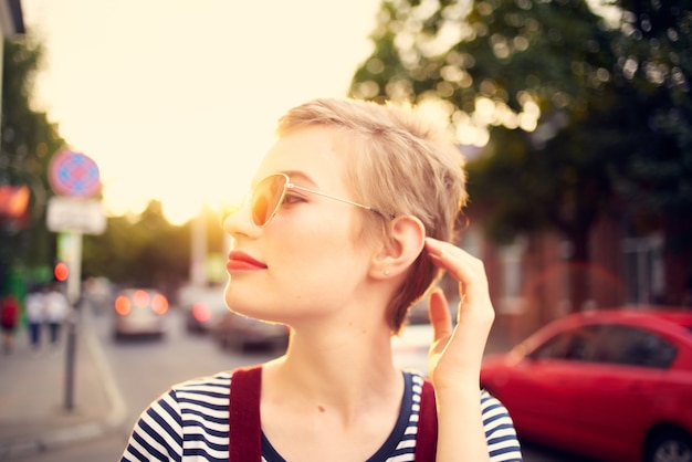 Uśmiechnięta kobieta w modnych okularach przeciwsłonecznych i spacer na świeżym powietrzu