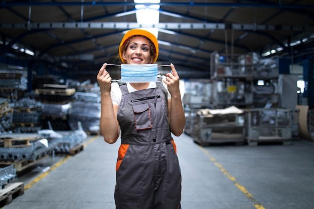 Uśmiechnięta kobieta w mundurze i kasku ochronnym zakładająca maskę higieniczną jako środek zapobiegający koronawirusowi