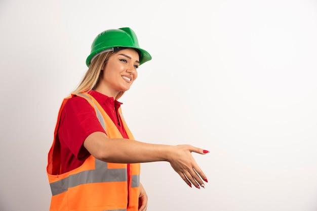 Uśmiechnięta kobieta w mundurze ochronnym i kasku pozowanie na białym tle.
